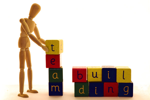 Team Building: Wooden artist's model demonstrating the art of team building with alphabet blocks.
