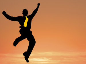 Business Leap: Business man leaping against a sunset sky