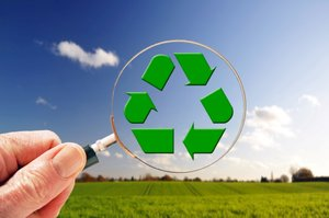Recycle: Recycling concept magnifying glass with recycle sign (non-copyright http://en.wikipedia.org/wiki/File:Recycling_symbol.svg) over a countryside background
