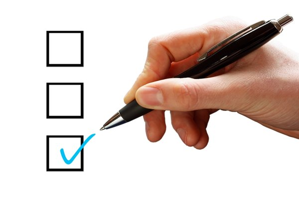 Tick Box: Hand with a pen and a blue tick in a box on a white background