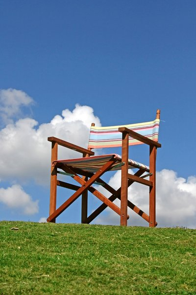 Canvas Garden Chair: Ordinary empty wooden framed garden chair against a blue sky