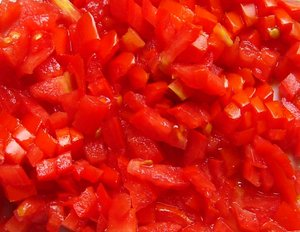 Tomatoes, Chopped or Diced: Fresh tomatoes diced or chopped, ready to cook or mix with other food.