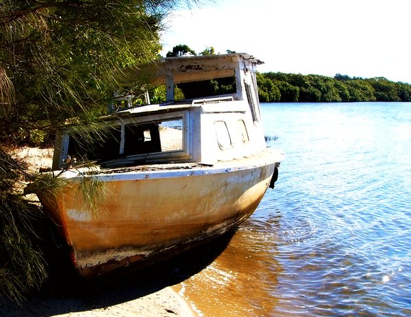 Abandoned Boat 2: An abandoned boat aground on the bank of a rivermouth. Sunlight playing on the water.