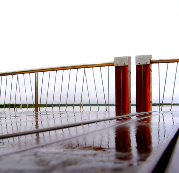 Sadness: A timber seat on a rainy day reflects the railings of a jetty or pier. It felt quite lonely.