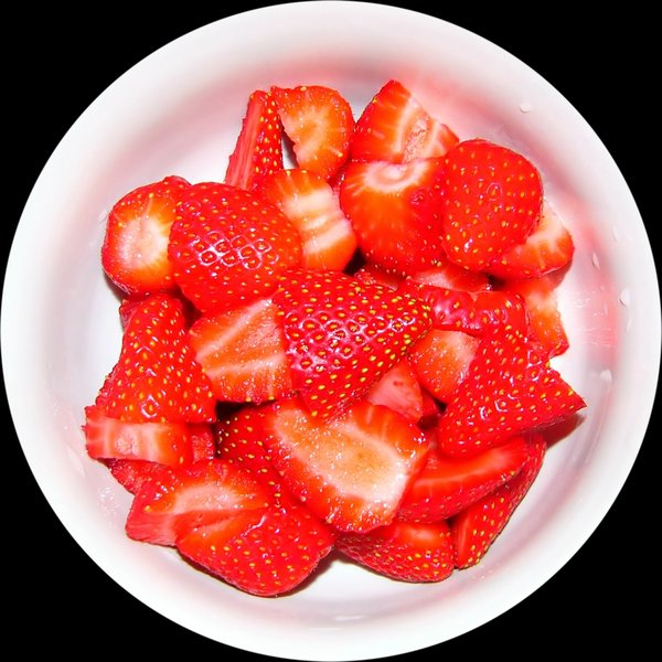 Succulent Strawberries: Succulent sliced strawberries in a white bowl against a black background.