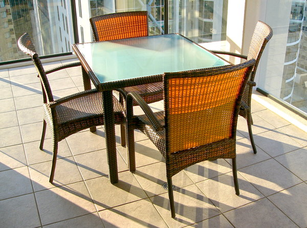 Outdoor Furniture: Outdoor table and chairs on a tiled inner city balcony in evening sunlight.
