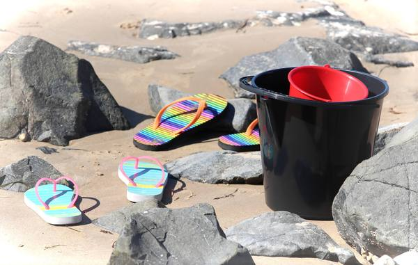 Buckets and Thongs: Buckets and children's thongs or flip flops on the sand at a rocky beach.