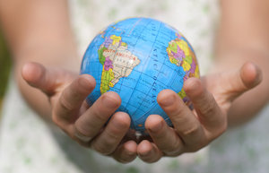 World care: globe in hands of little girl