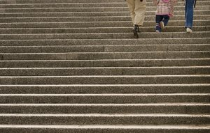 Three upstairs: Two adults and a child walking up some stone stairs